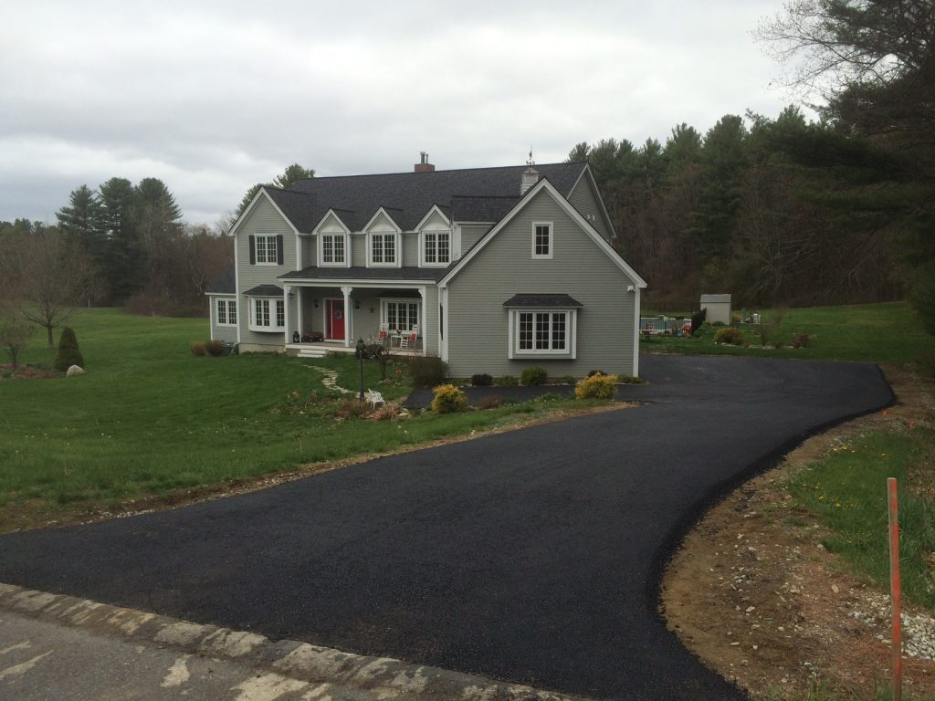Double story grey house with winding black asphalt driveway laid by Shattuck paving