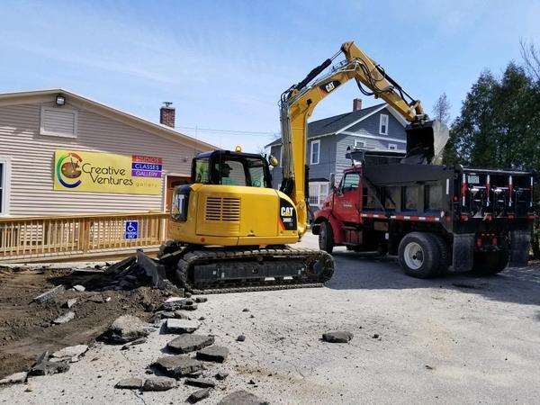Skid steer loader dumping asphalt into dump truck